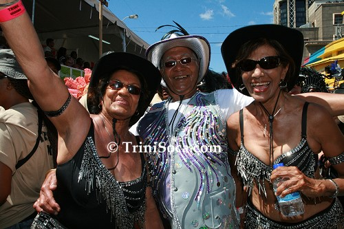 President George Maxwell Richards plays mas in Tribe with his wife Jean (L) and a friend